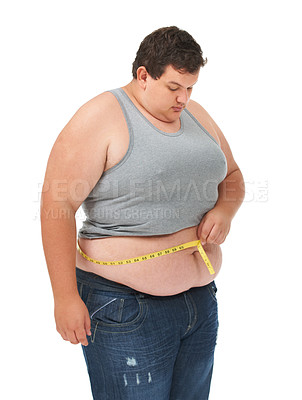 Buy stock photo An obese young man pulling in his stomach while measuring his waist with a measuring tape