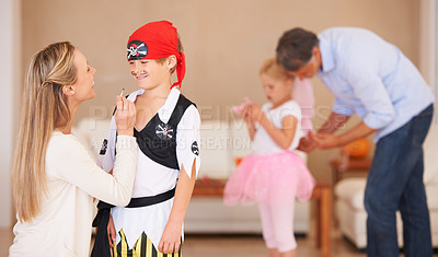 Buy stock photo A smiling boy standing in front of his mother who is painting a mustache on his face with father and sister in the background