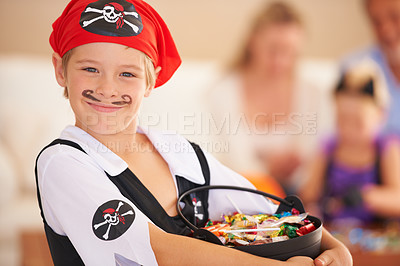 Buy stock photo A little boy dressed in a pirate costume and holding a basket of sweets with family sitting in the background