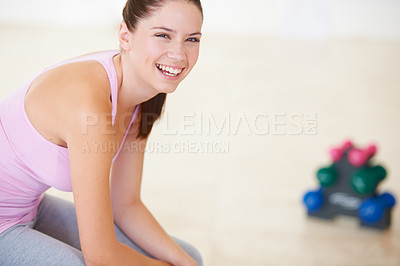 Buy stock photo Portrait of a young woman taking a break with dumbbells on the floor behind her