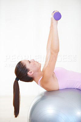 Buy stock photo Shot of a young woman lying back on an exercise ball and lifting weights
