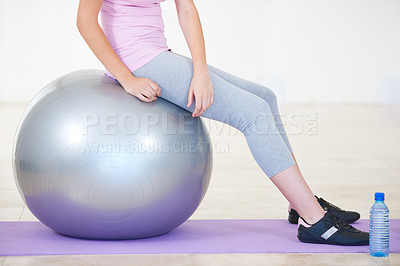 Buy stock photo Cropped shot of a woman sitting on an exercise ball next to a bottle of water