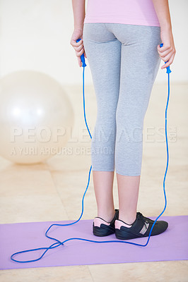 Buy stock photo Rearview cropped shot of a young woman standing on an exercise mat holding a skipping rope