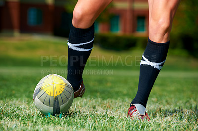 Buy stock photo Cropped shot of rugby player kicking a ball