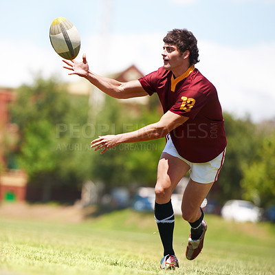 Buy stock photo Full length shot of a young rugby player receiving a pass