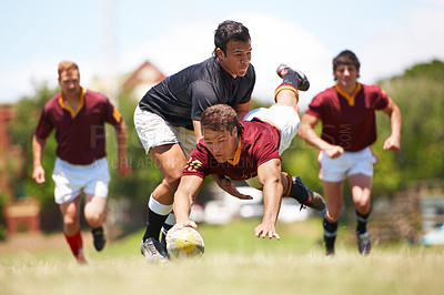 Buy stock photo Full length shot of a young rugby player scoring a try mid tackle