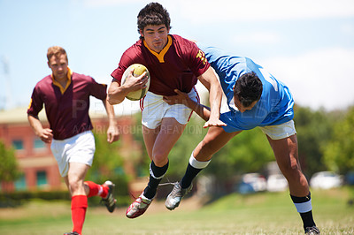 Buy stock photo Full length shot of a young rugby player trying to avoid a tackle