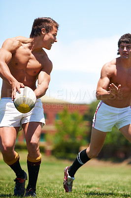 Buy stock photo Shot of two shirtless young rugby players going through a passing drill