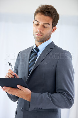 Buy stock photo A handsome businessman standing with a suit and tie and looking at a notebook in hand