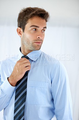 Buy stock photo A handsome businessman standing and peeking over his shoulder while adjusting his tie