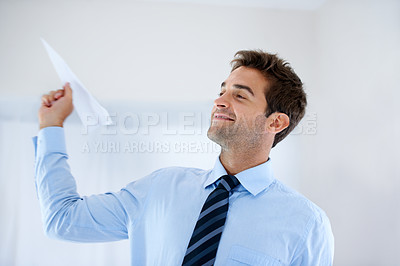 Buy stock photo A smiling businessman holding a paper plane and getting ready to throw it into the air