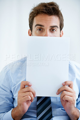 Buy stock photo Portrait of a business man holding a piece of papper in front of his face at work