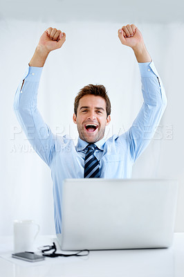 Buy stock photo Portrait of a businessman sitting at his desk with his computer in front of him and cheering with his arms raised above his head