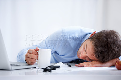 Buy stock photo A businessman asleep on his desk at work with a coffee in his hand