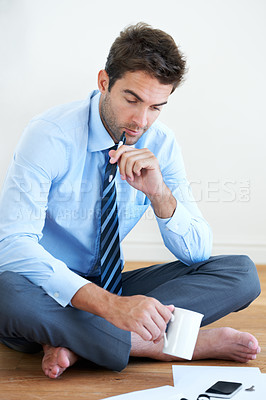 Buy stock photo A businessman looking over his paperwork with pen in hand