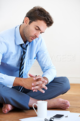 Buy stock photo A barefoot businessman sitting on the floor and looking over his paper work