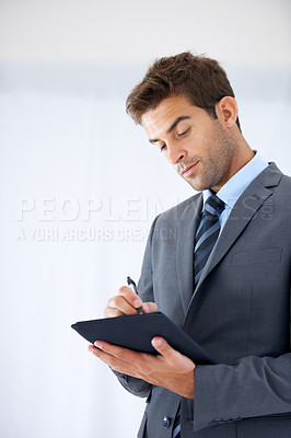 Buy stock photo A businessman writing in a note book with copyspace