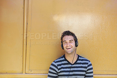 Buy stock photo A handsome young man smiling happily while listening to music through his headphones