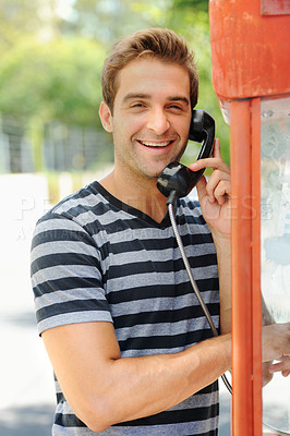 Buy stock photo A handsome young man smiling and having a conversation on a public telephone