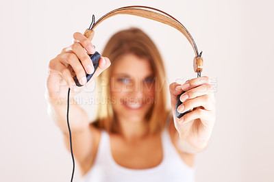 Buy stock photo A young woman holding out her headphones to you