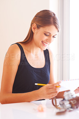 Buy stock photo A smiling young woman reading the address on an envelope with a vintage camera lying in the foreground