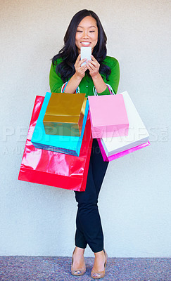 Buy stock photo A young asian woman sending a text message while shopping