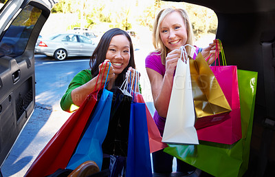 Buy stock photo Two woman packing their shopping bags into the boot of a car
