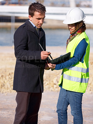 Buy stock photo Shot of a young construction worker going over some plans with the architect