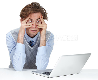 Buy stock photo A young man grimacing through his fingers while sitting next to his laptop