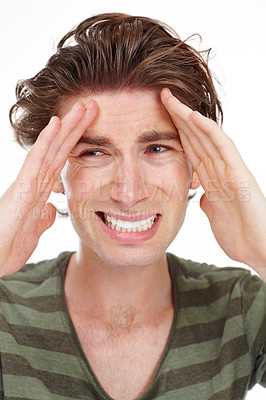 Buy stock photo Young man holding his forehead with an expression of frustration