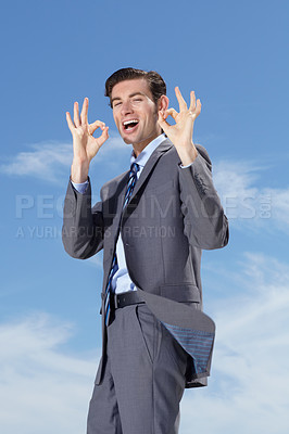 Buy stock photo A young businessman giving you an 'a okay' against a blue sky