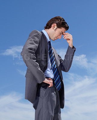 Buy stock photo A young businessman standing against a blue sky dejectedly