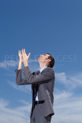 Buy stock photo A young businessman pleading to the sky for answers