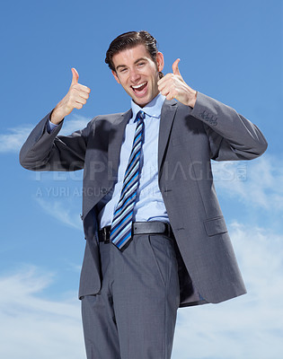 Buy stock photo A young businessman giving you a thumbs up against a blue sky