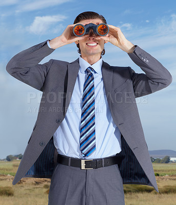 Buy stock photo A young businessman holding binoculars while standing against a blue sky
