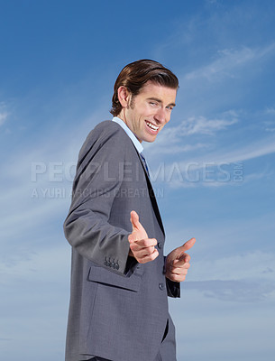 Buy stock photo A confident young businessman pointing at you against a blue sky