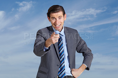 Buy stock photo A young businessman pointing at you against a blue sky