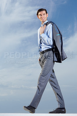 Buy stock photo Full body of a young businessman with his jacket over his shoulder against a blue sky