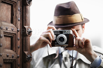 Buy stock photo Detective capturing a photo from around the corner while using a retro camera