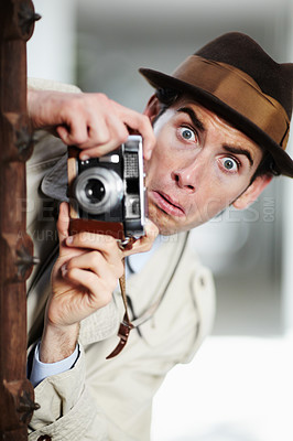 Buy stock photo Private detective capturing a photo suspiciously from around a corner while using a retro camera