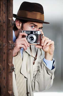 Buy stock photo Reporter capturing a photo suspiciously from around a corner while using a retro camera