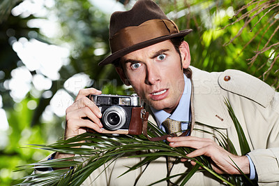 Buy stock photo Reporter taking a photo with a shocked expression from a thicket of bushes