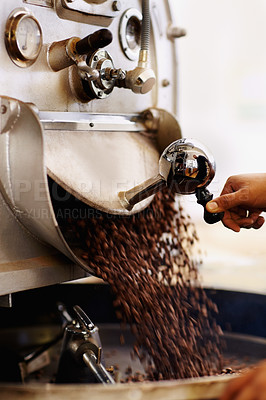 Buy stock photo Shot of coffee beans pouring into an industrial grinding machine