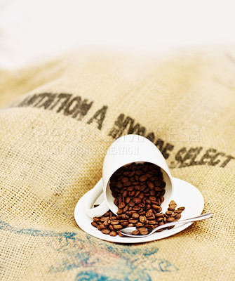 Buy stock photo Shot of a cup spilling coffee beans out onto a saucer and burlap sack