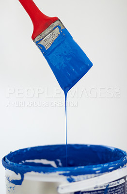 Buy stock photo Closeup of a paintbrush dripping blue paint into a bucket