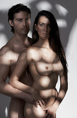 Buy stock photo A young nude couple standing in a dark studio