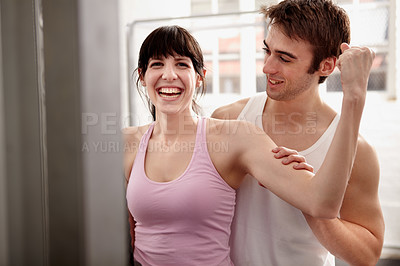Buy stock photo Shot of an attractive young woman being assessed by a personal trainer