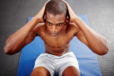 Buy stock photo Overhead shot of a focused man doing sit-ups on a mat in the gym.