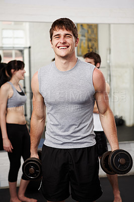 Buy stock photo Young man laughing while holding weights in a private gym