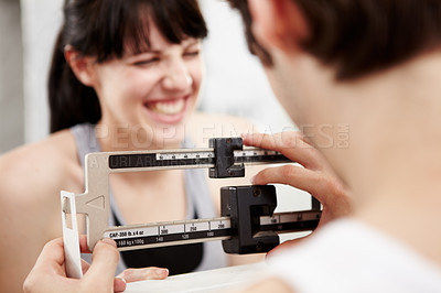 Buy stock photo Closeup cropped shot of a woman looking excited as her trainer measures her weight
